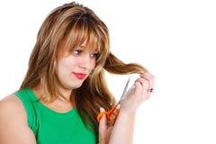 Jonge vrouw die haar haar snijdt Stock Fotografie