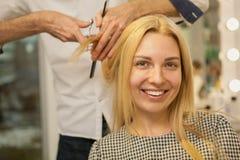 Jonge vrouw die haar die haar hebben door kapper wordt gestileerd stock afbeeldingen
