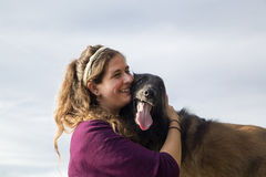 Jonge vrouw die haar hond koesteren Royalty-vrije Stock Afbeeldingen