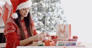 Jonge vrouw die haar Kerstmisgiften verfraaien stock videobeelden
