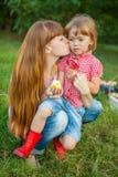 Jonge vrouw die haar kussen weinig dochter Royalty-vrije Stock Afbeeldingen