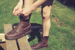 Jonge vrouw die haar laarzen binden stock foto