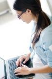 Jonge vrouw die haar laptop thuis met behulp van royalty-vrije stock afbeeldingen