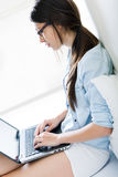 Jonge vrouw die haar laptop thuis met behulp van stock afbeeldingen
