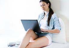 Jonge vrouw die haar laptop thuis met behulp van stock foto's