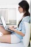 Jonge vrouw die haar laptop thuis met behulp van royalty-vrije stock foto