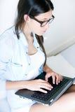Jonge vrouw die haar laptop thuis met behulp van royalty-vrije stock foto's