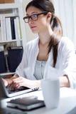 Jonge vrouw die haar laptop thuis met behulp van stock fotografie