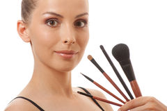 Jonge vrouw die haar make-upborstels tonen stock afbeelding