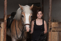 Jonge vrouw die haar paard in stal houden Stock Foto's