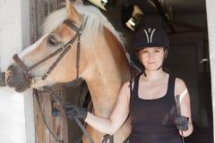 Jonge vrouw die haar paard voor de stal houden Stock Foto