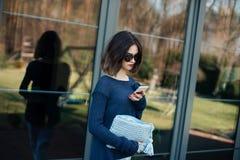 Jonge vrouw die haar smartphone op terras gebruiken royalty-vrije stock afbeeldingen