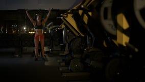 Jonge vrouw die haar sterkte testen door een barbell te houden stock video