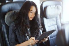 Jonge vrouw die haar tabletcomputer met behulp van terwijl het reizen door trein Het concept van de reistoepassing royalty-vrije stock foto's