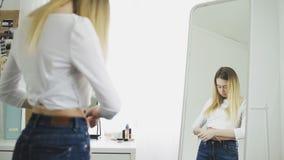 Jonge vrouw die haar taille meet stock video