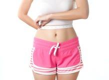 Jonge vrouw die haar taille met het meten van band meten Royalty-vrije Stock Afbeelding