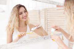 Jonge vrouw die haar tanden borstelt Stock Afbeeldingen