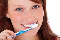 Jonge vrouw die haar tanden borstelt Stock Foto's
