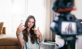 Jonge vrouw die haar video op camera opgezet op driepoot registreren royalty-vrije stock afbeeldingen