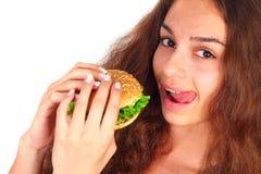 Jonge vrouw die hamburger eet stock afbeeldingen