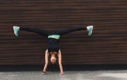 Jonge vrouw die handstand op stadsstraat doen royalty-vrije stock fotografie