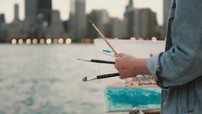 Jonge vrouw die het beeld trekken op de kust van het meer van Michigan, Chicago, Amerika Straatkunstenaar die borstels en verf ge stock video