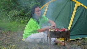 Jonge vrouw die in het bos op de achtergrond van een tent is draait de barbecue op de grill algemeen plan stock video