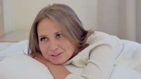 Jonge vrouw die het charminlgy liggen op een hoofdkussen glimlachen stock videobeelden