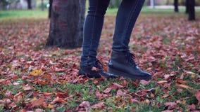 Jonge vrouw die in het de herfstpark lopen Vrouwelijke voeten close-up meisje die op gevallen bladeren lopen stock footage