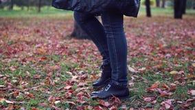 Jonge vrouw die in het de herfstpark lopen Vrouwelijke voeten close-up meisje die op gevallen bladeren lopen stock videobeelden