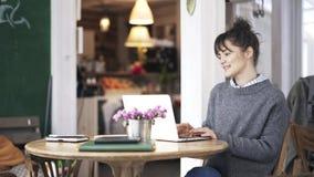 Jonge vrouw die in het grijs een sweater glimlachen en Web in een koffie surfen stock video