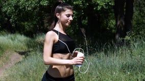 Jonge vrouw die in het hout lopen Het meisje is bezig geweest met sporten stock videobeelden
