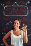 Jonge vrouw die het o.k. teken stellen tonen tegen verkoopreclame Royalty-vrije Stock Foto