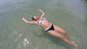 Jonge vrouw die het ontspannen op de golven in mooi azuurblauw carribean van de overzeese de vakantieconcept vakantiepret leggen stock footage