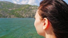 Jonge vrouw die het overzees en de bergen bewonderen stock video