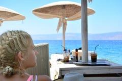 Jonge vrouw die het overzees van strandtoevlucht bekijken Royalty-vrije Stock Afbeeldingen