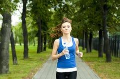 Jonge vrouw die in het park in de zomer aanstoot Royalty-vrije Stock Fotografie