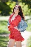 Jonge vrouw die in het park lopen De scène van de schoonheidsaard met kleurrijke achtergrond De maniervrouw met fles van drank on stock foto's