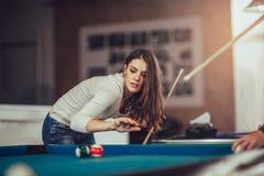 Jonge vrouw die het snookerschot pogen te nemen stock fotografie