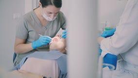 Jonge vrouw die het tandartsbureau bezoeken Vrouwelijke zitting als tandvoorzitter terwijl de arts die haar mond controleren stock videobeelden
