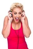 Jonge vrouw die het verraste luisteren aan muziek kijkt Stock Foto's