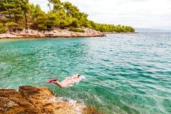 Jonge vrouw die in het water springt royalty-vrije stock foto