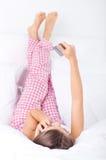 Jonge vrouw die het winkelen over de telefoon in bed maakt Stock Afbeelding