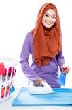 Jonge vrouw die hijab het strijken kleren dragen en het bespuiten van parfum Royalty-vrije Stock Afbeeldingen