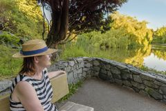 Jonge vrouw die in hoed en gestreepte kleding op de vijver in de zomerdag kijken royalty-vrije stock fotografie