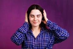 Jonge vrouw die in hoofdtelefoons aan muziek luistert royalty-vrije stock afbeelding