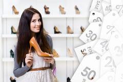 Jonge vrouw die hoog gehielde schoen op verkoop houden Royalty-vrije Stock Foto's