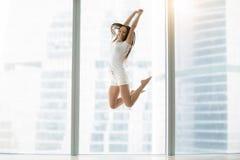 Jonge vrouw die hoog springt stock foto's
