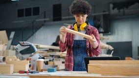 Jonge vrouw die houten planken met schuurpapierblok oppoetsen in workshop stock video