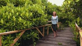 Jonge vrouw die houten promenade in mangroven lopen stock video